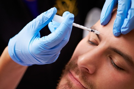 31066865 - man having botox treatment at beauty clinic