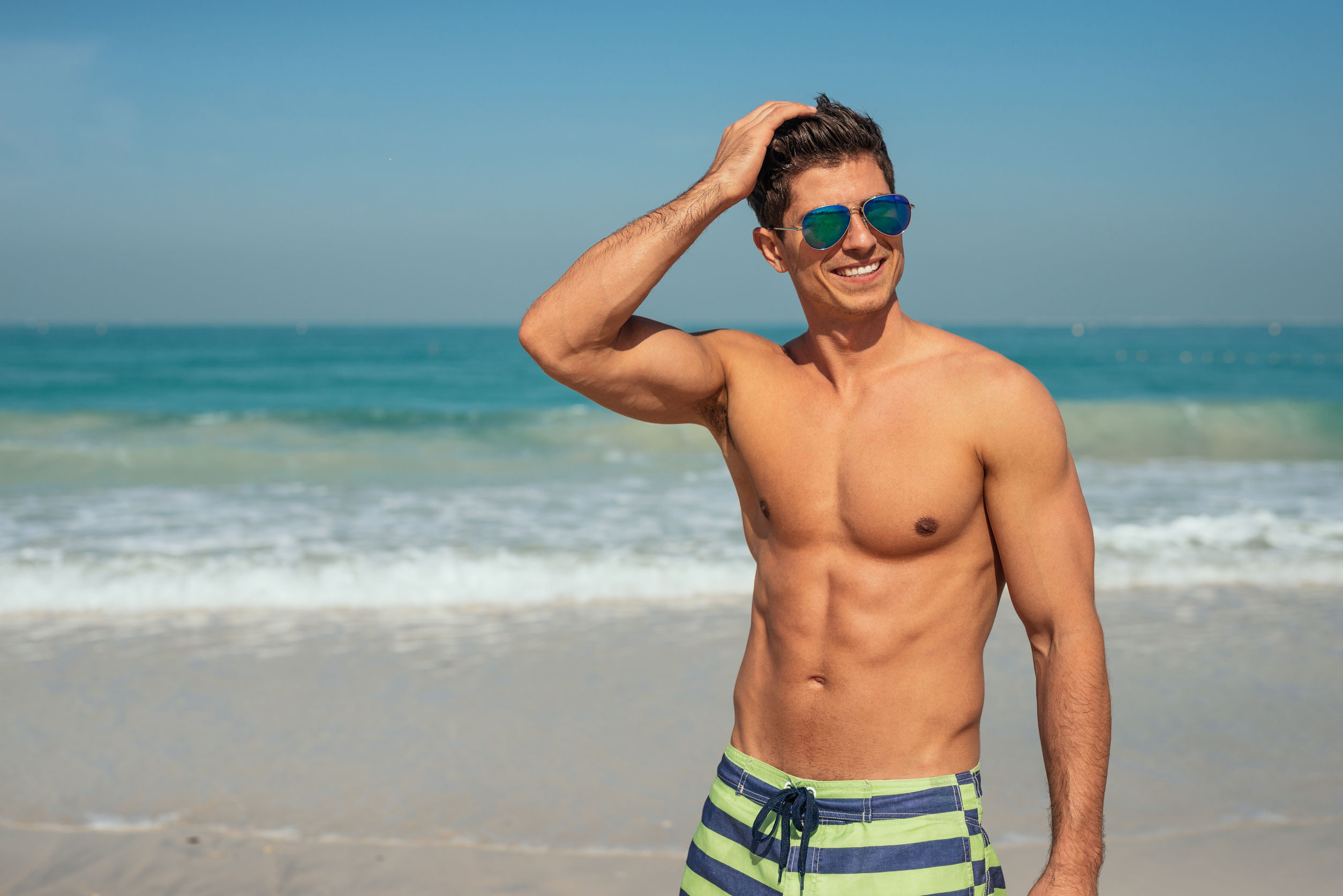 62373054 - handsome smiling man enjoying day on the beach.